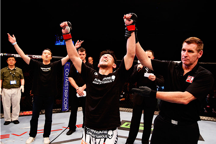 SINGAPORE - JANUARY 04:  Tatsuya Kawajiri celebrates his win over Sean Soriano in their featherweight bout during the UFC Fight Night event at the Marina Bay Sands Resort on January 4, 2014 in Singapore. (Photo by Mitch Viquez/Zuffa LLC/Zuffa LLC via Gett
