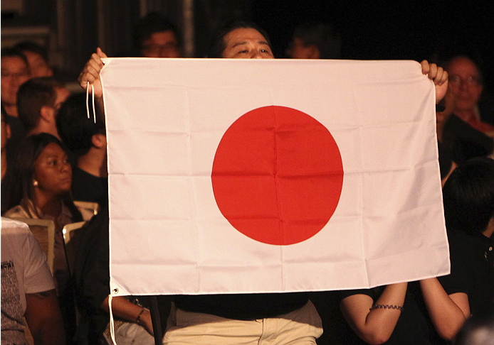 SINGAPORE - JANUARY 04:  A fan holds a Japanese flag during Katsunori Kikuno and Quinn Mulhern's during their lightweight bout during the UFC Fight Night event at the Marina Bay Sands Resort on January 4, 2014 in Singapore. (Photo by Mitch Viquez/Zuffa LL