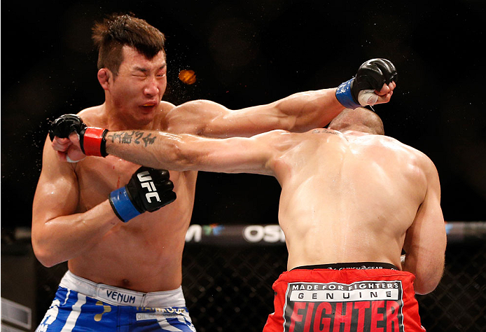SINGAPORE - JANUARY 04:  (R-L) Tarec Saffiedine and Lim Hyun Gyu trade punches in their welterweight bout during the UFC Fight Night event at the Marina Bay Sands Resort on January 4, 2014 in Singapore. (Photo by Josh Hedges/Zuffa LLC/Zuffa LLC via Getty