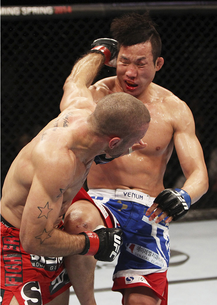 SINGAPORE - JANUARY 04:  Tarec Saffiedine lands a shot on Lim Hyun Gyu  in their welterweight bout during the UFC Fight Night event at the Marina Bay Sands Resort on January 4, 2014 in Singapore. (Photo by Mitch Viquez/Zuffa LLC/Zuffa LLC via Getty Images