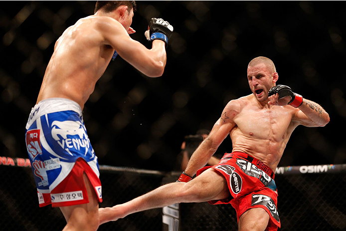 SINGAPORE - JANUARY 04:  (R-L) Tarec Saffiedine kicks Lim Hyun Gyu in their welterweight bout during the UFC Fight Night event at the Marina Bay Sands Resort on January 4, 2014 in Singapore. (Photo by Josh Hedges/Zuffa LLC/Zuffa LLC via Getty Images)