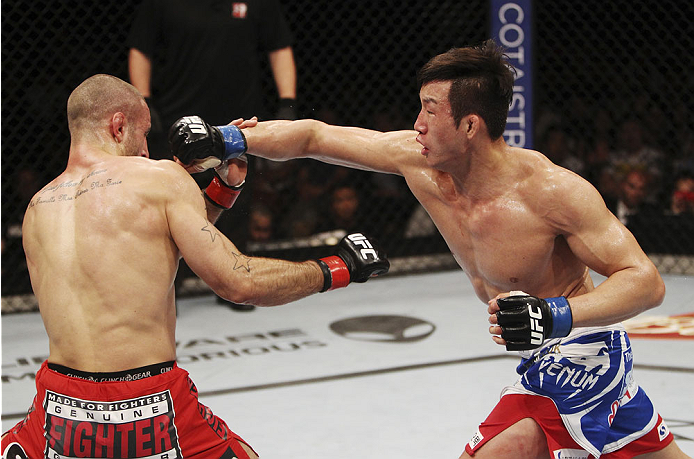 SINGAPORE - JANUARY 04:  Lim Hyun Gyu throws a punch at Tarec Saffiedine in their welterweight bout during the UFC Fight Night event at the Marina Bay Sands Resort on January 4, 2014 in Singapore. (Photo by Mitch Viquez/Zuffa LLC/Zuffa LLC via Getty Image