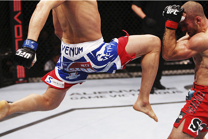 SINGAPORE - JANUARY 04:  Lim Hyun Gyu goes for a flying knee on Tarec Saffiedine in their welterweight bout during the UFC Fight Night event at the Marina Bay Sands Resort on January 4, 2014 in Singapore. (Photo by Mitch Viquez/Zuffa LLC/Zuffa LLC via Get