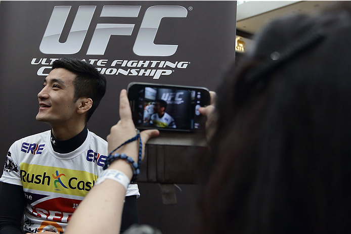SINGAPORE - JANUARY 02:  A lady takes a photo of Kyung Ho Kang during the UFC Fight Night Singapore Ultimate Media Day at the Skating Rink at The Shoppes at Marina Bay Sand on January 2, 2014 in Singapore.  (Photo by Suhaimi Abdullah/Zuffa LLC)