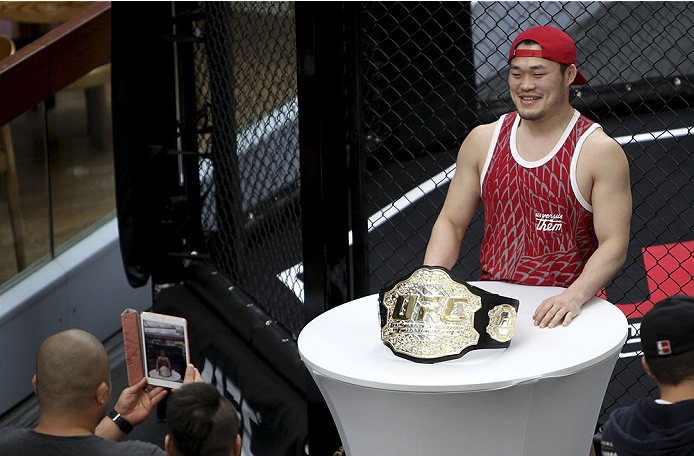 SINGAPORE - JANUARY 02:  A fan poses with the UFC championship belt during the UFC Fight Night Singapore Ultimate Media Day at the Shoppes at Marina Bay Sands on January 2, 2014 in Singapore. (Photo by Mitch Viquez/Zuffa LLC/Zuffa LLC via Getty Images)