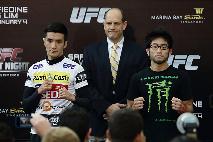 SINGAPORE - JANUARY 02:  Kyung Ho Kang (L) and Shunichi Shimizu (R) pose for a photo as Mark Fischer (C), managing director of UFC Asia, looks on during the UFC Fight Night Singapore Ultimate Media Day at the Skating Rink at The Shoppes at Marina Bay Sand