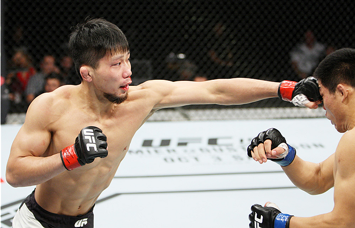 SAITAMA, JAPAN - SEPTEMBER 27: Keita Nakamura of Japan punches Li Jingliang of China  in their welterweight bout during the UFC event at the Saitama Super Arena on September 27, 2015 in Saitama, Japan. (Photo by Mitch Viquez/Zuffa LLC/Zuffa LLC via Getty