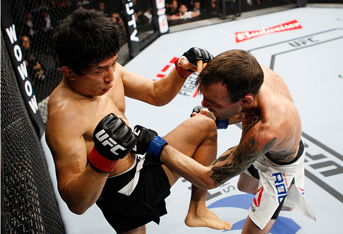 SAITAMA, JAPAN - SEPTEMBER 27:  Takeya Mizugaki of Japan throws a knee on George Roop of the United States of America in their bantamweight bout during the UFC event at the Saitama Super Arena on September 27, 2015 in Saitama, Japan. (Photo by Mitch Vique