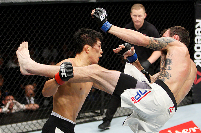 SAITAMA, JAPAN - SEPTEMBER 27: Takeya Mizugaki of Japan goes for a takedown on George Roop of the United States of America in their bantamweight bout during the UFC event at the Saitama Super Arena on September 27, 2015 in Saitama, Japan. (Photo by Mitch