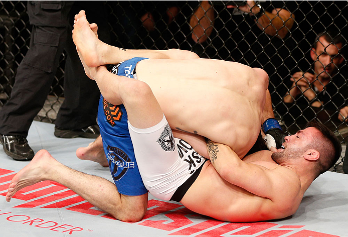 SAO PAULO, BRAZIL - MAY 31: (R-L) Pedro Munhoz attempts to secure a guillotine choke submission against Matt Hobar in their bantamweight fight during the UFC Fight Night event at the Ginasio do Ibirapuera on May 31, 2014 in Sao Paulo, Brazil. (Photo by Jo
