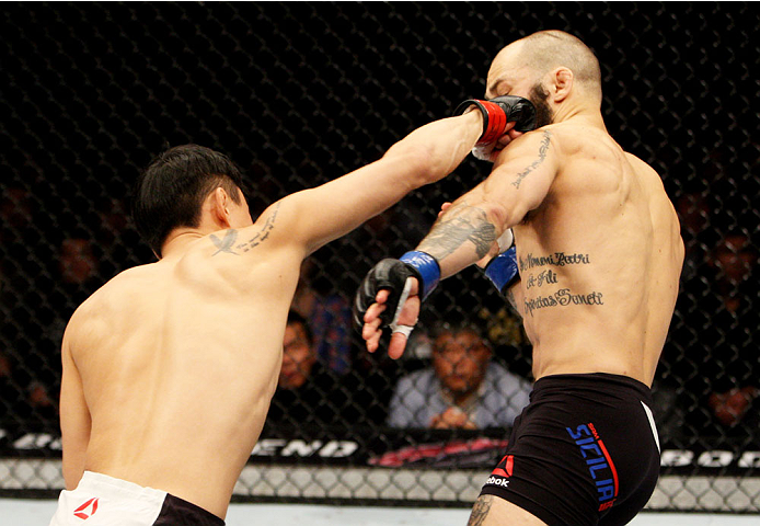 SEOUL, SOUTH KOREA - NOVEMBER 28: Doo Ho Choi of South Korea punches Sam Sicilia of the United States of America in their  featherweight bout during the UFC Fight Night at the Olympic Park Gymnastics Arena on November 28, 2015 in Seoul, South Korea. (Phot