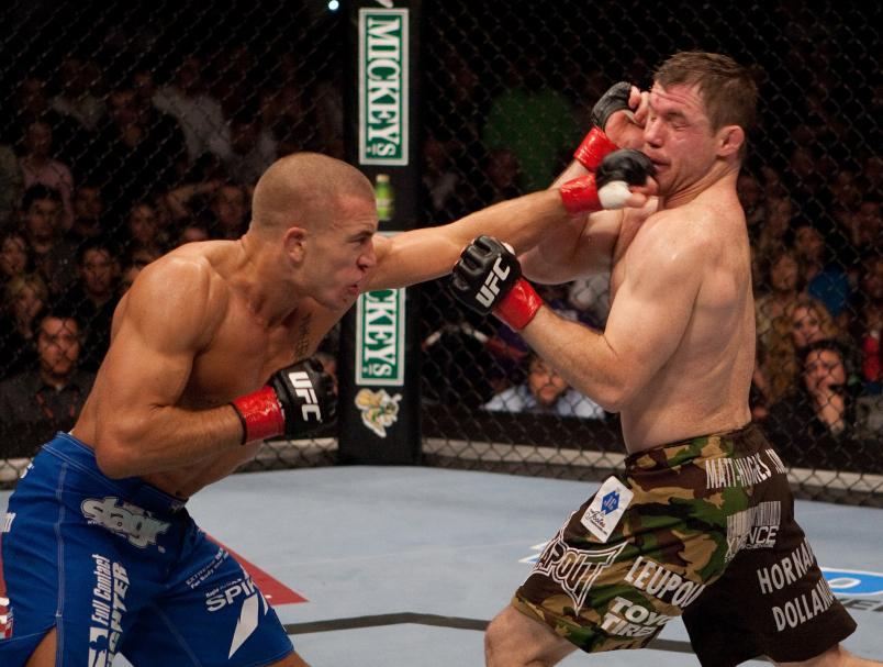(L-R) Georges St-Pierre punches Matt Hughes at UFC 65 at the Arco Arena on November 18, 2006 in Sacramento, California. (Photo by Josh Hedges/Zuffa LLC)