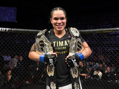 Amanda Nunes with her two belts at UFC 232