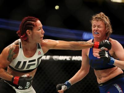 ANAHEIM, CA - JULY 29:  Cris Cyborg of Brazil punches Tonya Evinger in their UFC women's featherweight championship bout during the UFC 214 event at Honda Center on July 29, 2017 in Anaheim, California.  (Photo by Christian Petersen/Zuffa LLC/Zuffa LLC vi