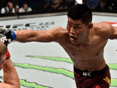PERTH, AUSTRALIA - FEBRUARY 11:  (R-L) Li Jingliang of China punches Jake Matthews of Australia in their welterweight bout during the UFC 221 event at Perth Arena on February 11, 2018 in Perth, Australia. (Photo by Jeff Bottari/Zuffa LLC/Zuffa LLC via Get